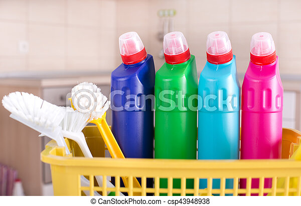 Cleaning supplies in kitchen. Plastic basket with different cleaning ...