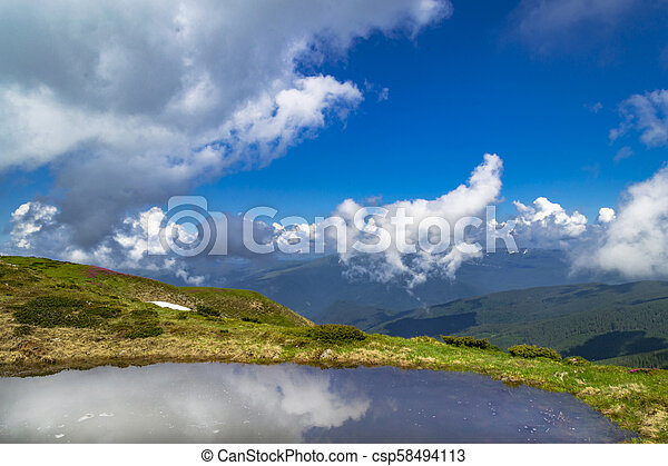 Clear Alpine lake with reflection of blue cloudy sky - csp58494113