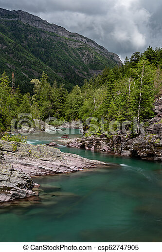 Clear Blue Water Curves Around Rocky Shore - csp62747905