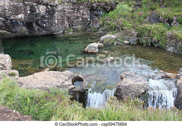Clear Green rocky pool in the Isle of Skye, Scotland - csp59475664
