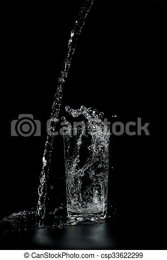 clear water pours into the a glass beaker - csp33622299