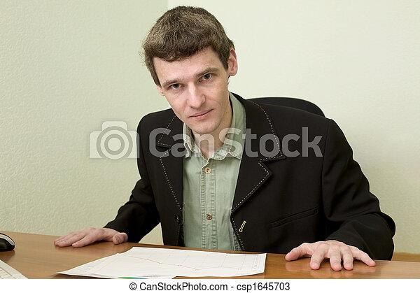 Clerk at office sits at a desktop - csp1645703