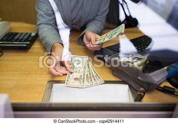 clerk giving cash money to customer at bank office - csp42914411