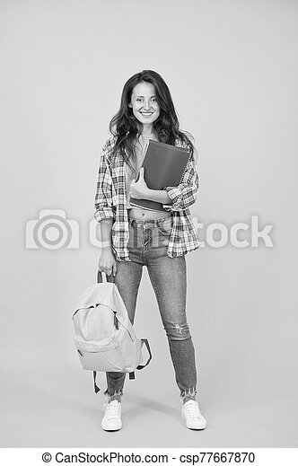 Clever forever. Girl student yello background. Happy girl back to school. Pretty girl borrow books in library. Smart girl smile in casual wear. Education and learning. Knowledge and skills - csp77667870