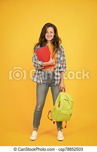 Clever forever. Girl student yello background. Happy girl back to school. Pretty girl borrow books in library. Smart girl smile in casual wear. Education and learning. Knowledge and skills - csp78852503