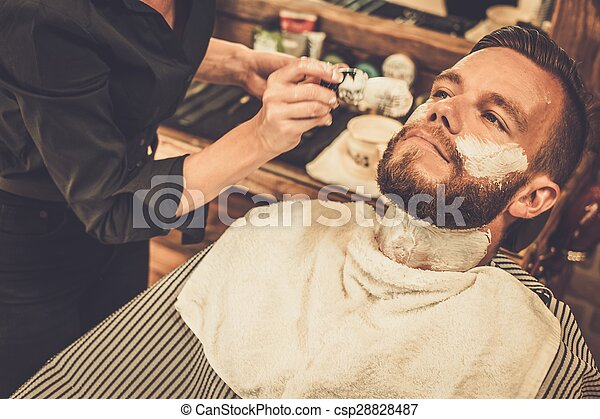 Client during beard shaving in barber shop - csp28828487