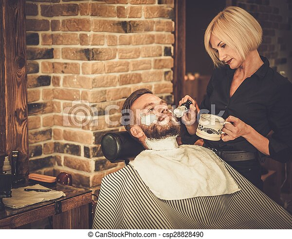 Client during beard shaving in barber shop - csp28828490