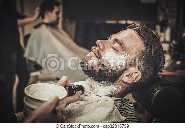 Client during beard shaving in barber shop - csp32816739