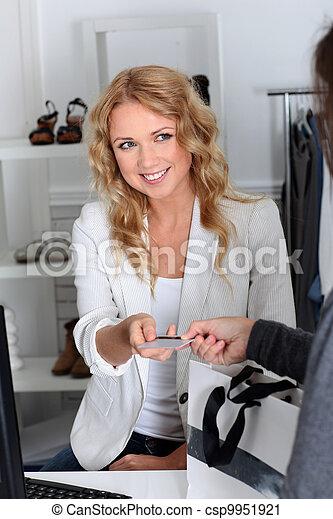 Cliente en una tienda de comercio pagando con tarjeta de crédito - csp9951921
