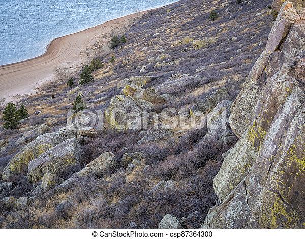 climbing cliff over mountain lake - csp87364300