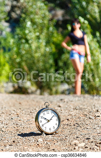 clock on the stone road and blurred girl at sunny day. - csp36634846