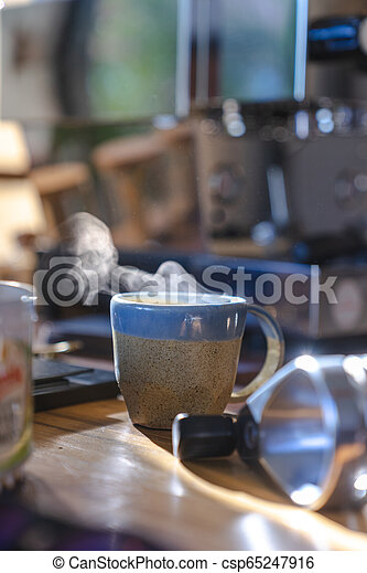 close up a ceramic cup of hot smoke coffee on wooden table with blurred coffee machine in background - csp65247916