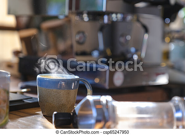 close up a ceramic cup of hot smoke coffee on wooden table with blurred coffee machine in background - csp65247950