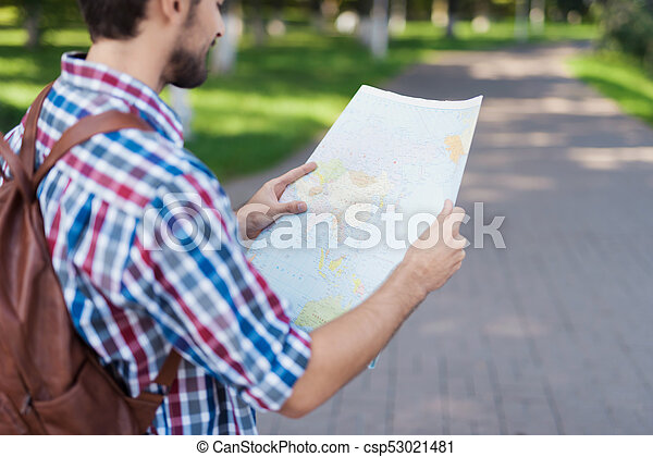 Close up. A man holds in his hands an expanded map of the world. He thinks where to go next. - csp53021481