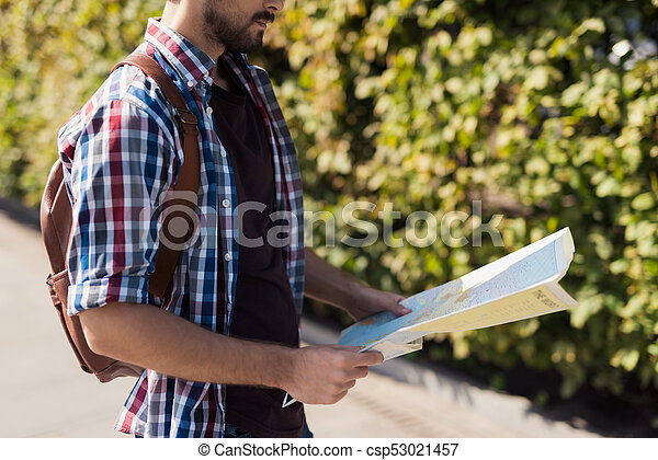 Close up. A man holds in his hands an expanded map of the world. He thinks where to go next. - csp53021457