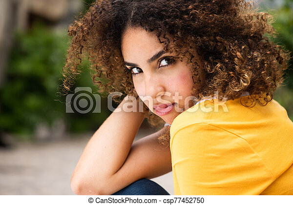 Close up attractive young african american woman with curly hair sitting outside - csp77452750