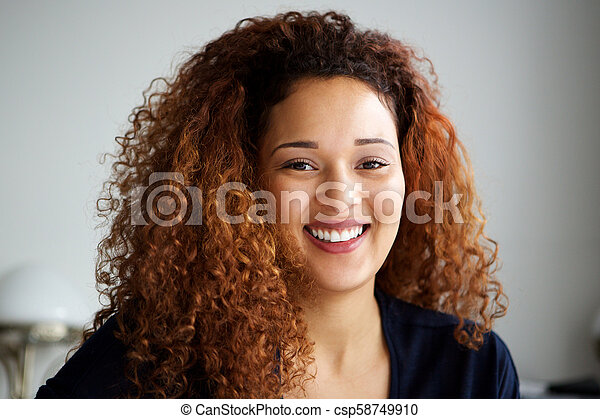 Close up attractive young woman with curly hair smiling - csp58749910