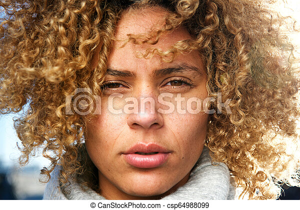 Close up beautiful african american woman with curly hair staring - csp64988099