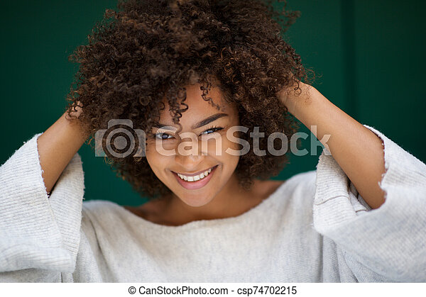 Close up beautiful young african american woman smiling with hands in hair - csp74702215