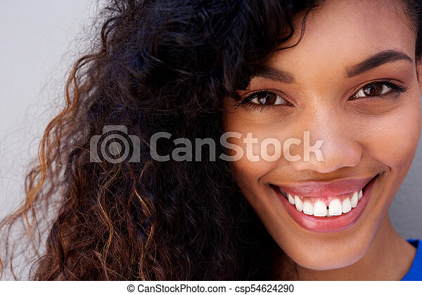 Close up beautiful young african american woman with curly hair smiling against gray backgorund - csp54624290