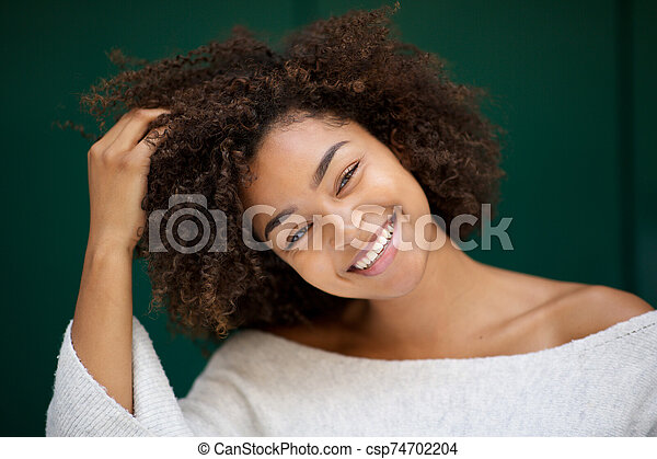 Close up beautiful young african american woman smiling with hand in hair - csp74702204