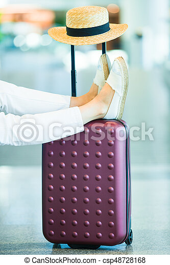 Close-up female legs, hat and baggage in airport indoor. Airline passenger in an airport waiting for flight aircraft - csp48728168