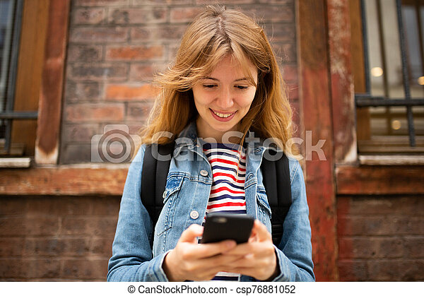 Close up front of smiling young woman looking at mobile phone in city - csp76881052
