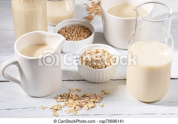 Close-up glass bottle and mug with oat milk and bowls with oat seeds and flakes on white wooden table. - csp70696141
