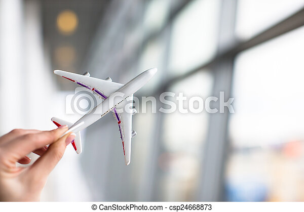 Close up hand holding an airplane model at airport - csp24668873