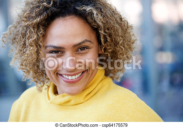 Close up happy african american woman with curly hair - csp64175579