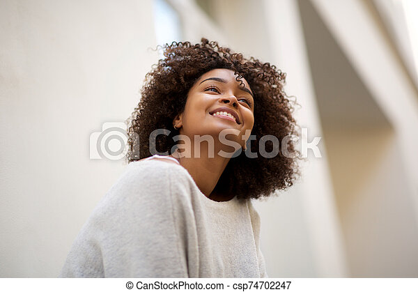 Close up happy african american woman with curly hair smiling outside - csp74702247