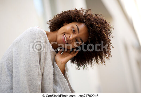 Close up happy young african american woman with curly hair smiling outside - csp74702246