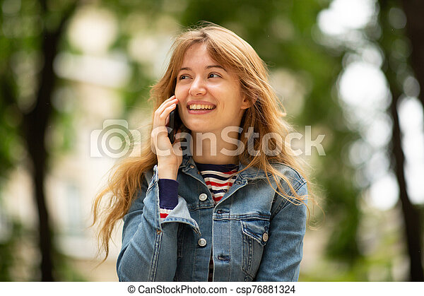 Close up happy young woman talking with mobile phone in park - csp76881324
