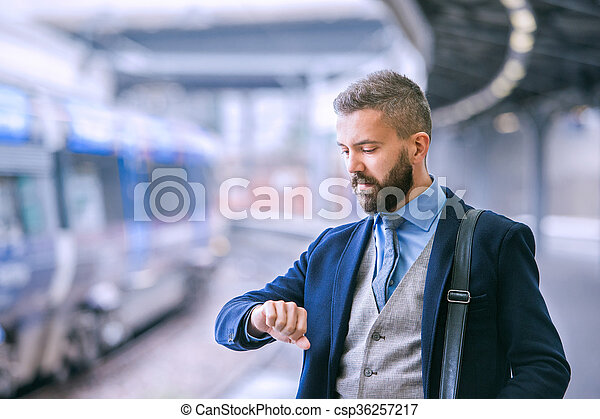 Close up, hipster businessman waiting at the train station - csp36257217