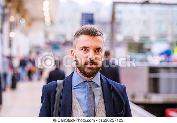 Close up, hipster businessman waiting at the train station - csp36257123