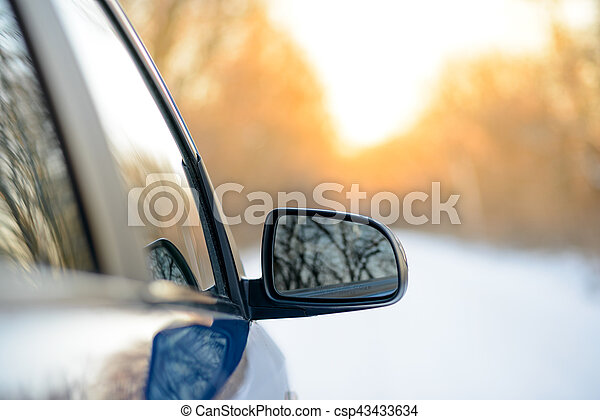 Close up Image of Side Rear-view Mirror on a Car in the Winter Landscape with Evening Sun - csp43433634