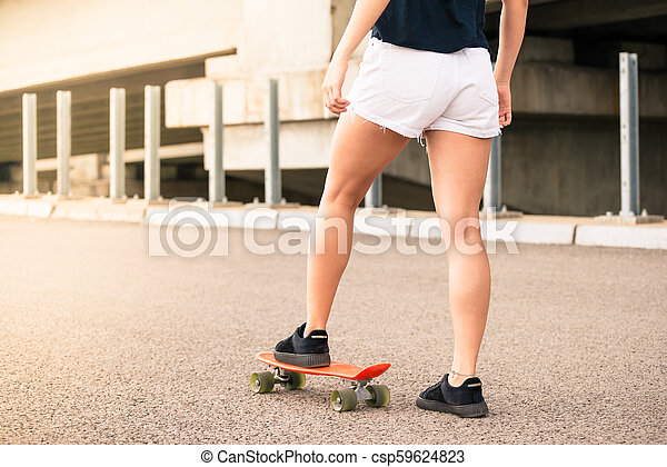 Close up Image of Young Girl`s Legs and Orange Skateboard - csp59624823
