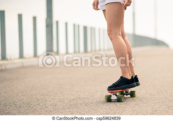 Close up Image of Young Girl`s Legs Riding Orange Skateboard - csp59624839