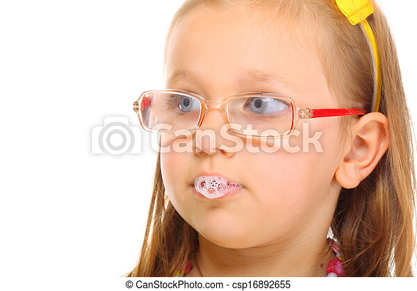 Close up little girl in glasses doing fun saliva bubbles - csp16892655