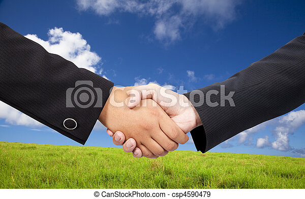 Close-up of a business people shaking hands against blue sky and green background  - csp4590479