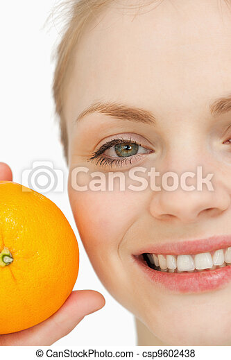 Close up of a cheerful woman holding an orange - csp9602438