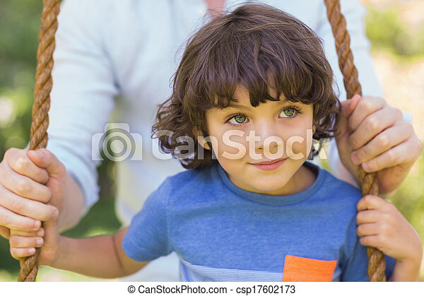 Close-up of a father pushing cute boy on swing - csp17602173