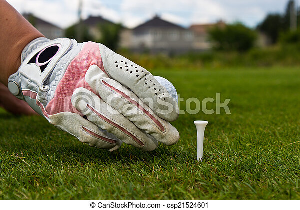 Close-up of a gloved hand of a female golfer placing golf ball o - csp21524601
