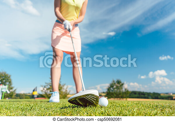 Close-up of a golf ball next to a professional club held by a fe - csp50692081
