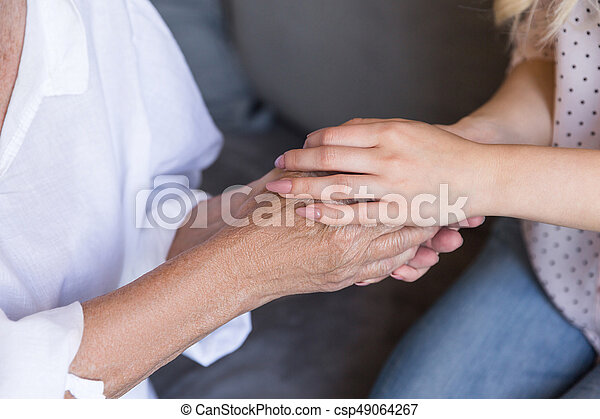 Close up of a granddaughter and grandmother holding hands - csp49064267