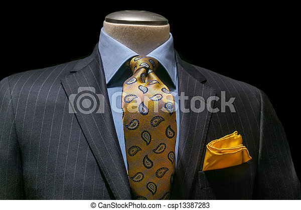 Close-up of a gray striped jacket with blue shirt, patterned golden yellow tie and handkerchief on black background. Clipping path included. - csp13387283