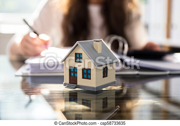 Close-up Of A House Model On Glass Desk - csp58733635