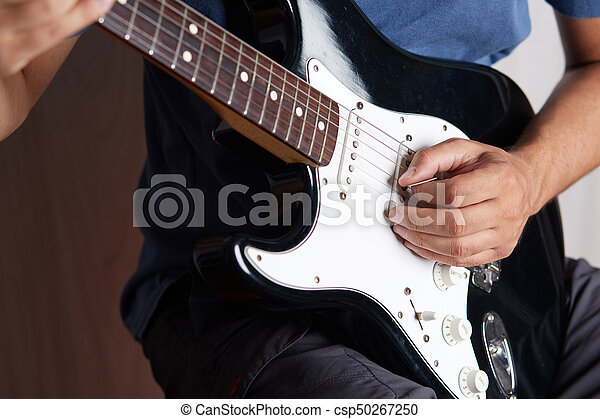 Close up of a lefty electric guitar being played - csp50267250