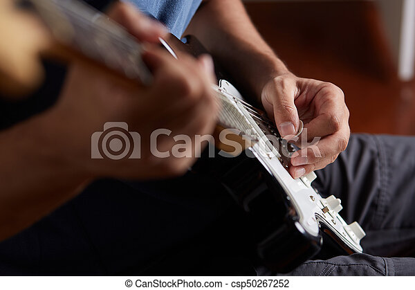 Close up of a lefty electric guitar being played - csp50267252