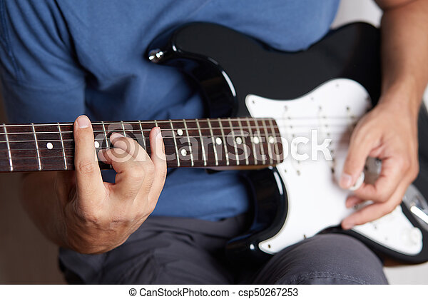 Close up of a lefty electric guitar being played - csp50267253